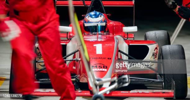rode auto bij pitstop - gemotoriseerde sport stockfoto's en -beelden