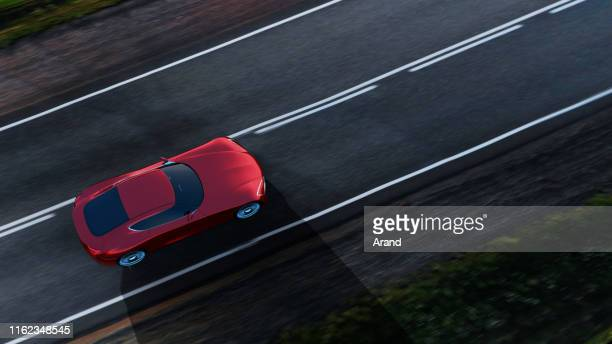 red car driving on a road - futuristic car stock pictures, royalty-free photos & images