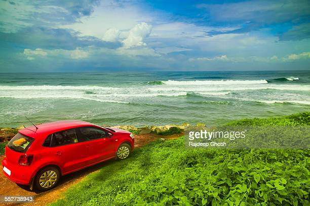 Red car, green grass, blue sea and sky in kerala