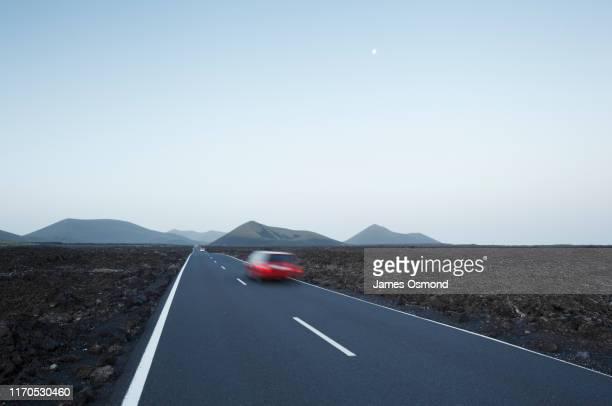 red car in blurred motion travelling on straight road crossing lava plains towards distant volcanoes. - rijden een motorvoertuig besturen stockfoto's en -beelden