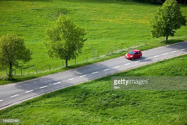 Rotes Auto auf der Landstraße, Frühling, Luftaufnahme
