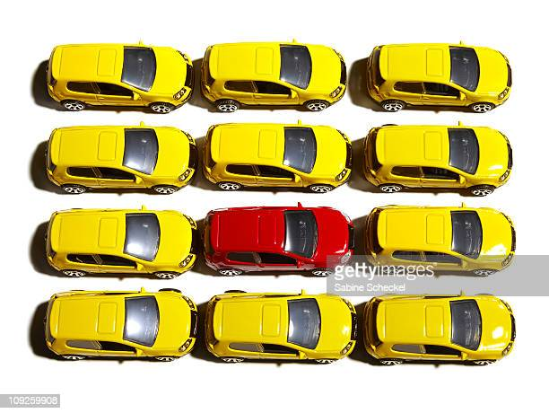 red car surrounded by yellow cars