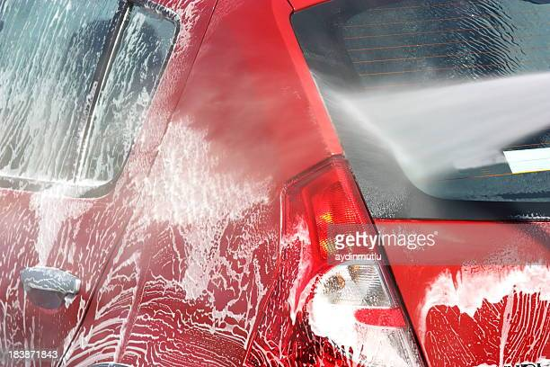 Red car undergoing a soapy car wash