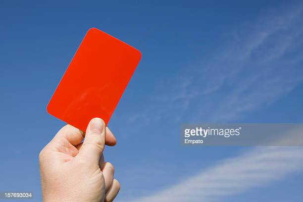 Red card held up against a blue sky.