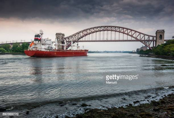 Red cargo ship under the Hell Gate Bridge over the East River