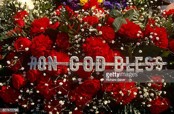 Red carnations and roses form a cortege memorial to notorious 60s gangster twin Ronnie Kray during East End funeral The words Ron God Bless are...