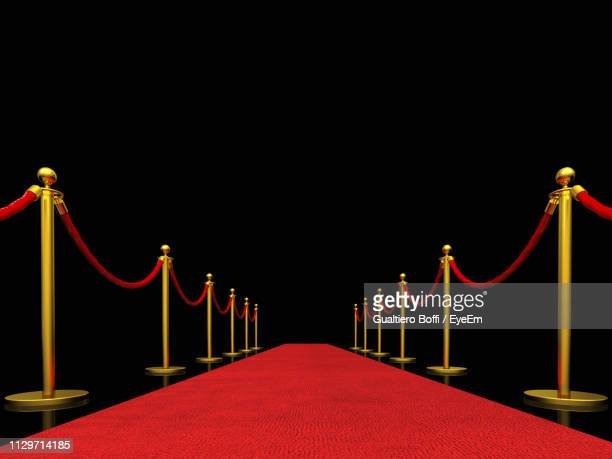 red carpet event amidst bollards against black background - red carpet event stock pictures, royalty-free photos & images
