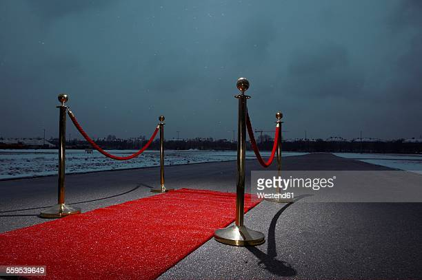 red carpet on street, city in the background, dark clouds - gala stockfoto's en -beelden