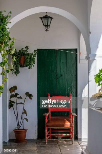 red chair against a green door in a patio - finn bjurvoll stockfoto's en -beelden