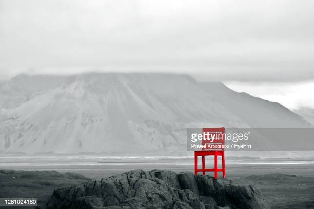 red chair on rocky hill with scenic view of mountains in background during cloudy afternoon - moment of silence stock pictures, royalty-free photos & images
