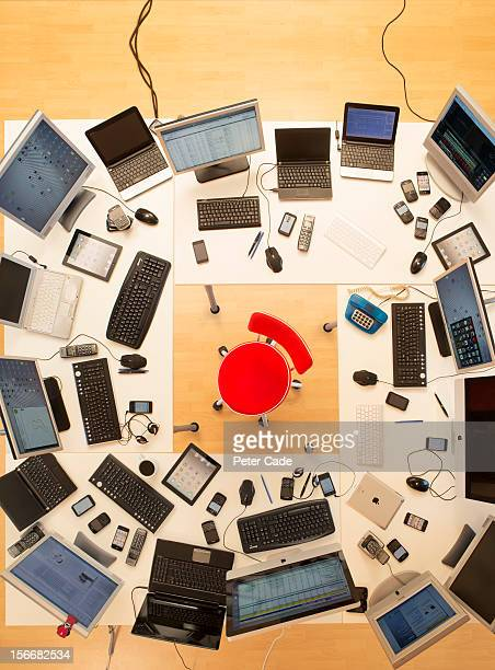 Red chair surrounded by desks covered in computers