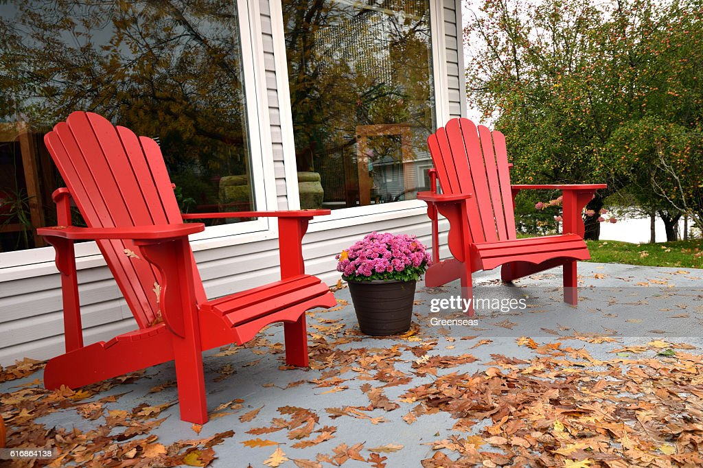 Red Chairs surrounded by Autumn Leaves : Stock Photo