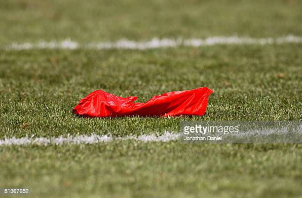 A red challenge flag rests on the field after head coach Lovie Smith of the Chicago Bears questioned a fumble against the Detroit Lions on September...