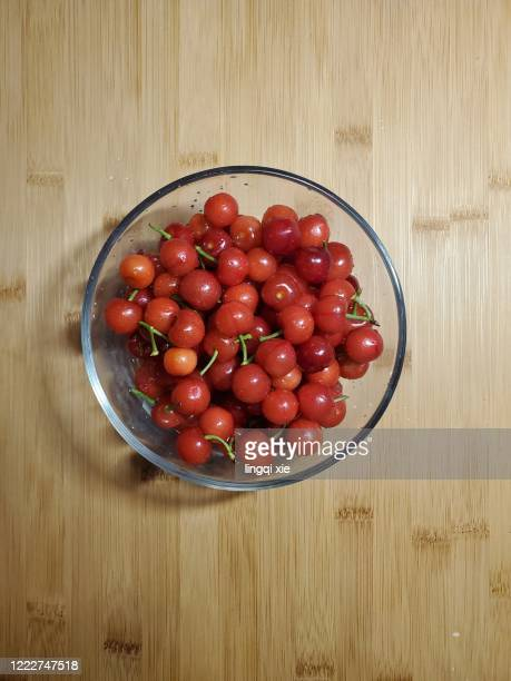 red cherries in a glass bowl on a bamboo table - サワーチェリー ストックフォトと画像