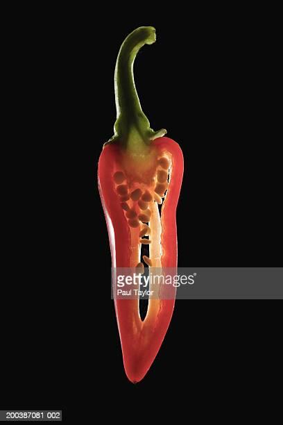 red chile pepper sliced in half - scharfe schoten stock-fotos und bilder