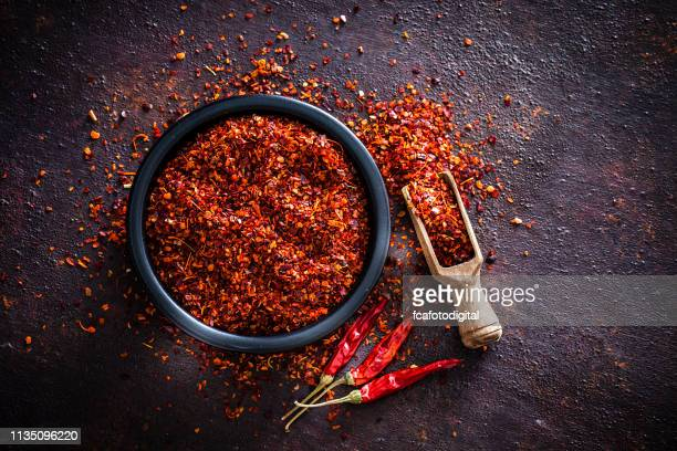 red chili pepper flakes shot from above - spice stock pictures, royalty-free photos & images