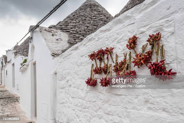 Red Chili Peppers Drying On Wall Of Trulli House Against Cloudy Sky