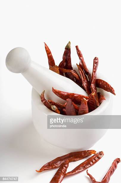 Red chili peppers in a mortar with pestle