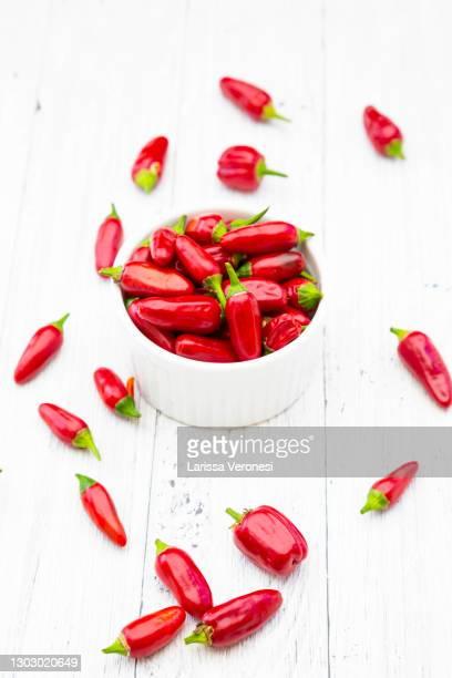 red chili peppers on white wood - larissa veronesi stock-fotos und bilder