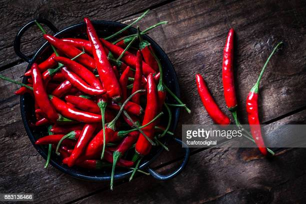 red chili peppers shot from above on rustic wooden table - chili stock photos and pictures