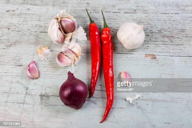 red chili pods, red onion and garlic on wood - cabeza de ajos fotografías e imágenes de stock