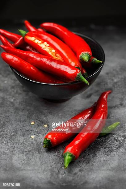 Red chilis in bowl on moody background.