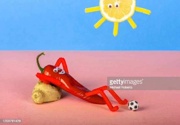 red chilli pepper with anthropomorphic smiley face sunbathing under lemon sun with plain pink and blue background - still life stock pictures, royalty-free photos & images