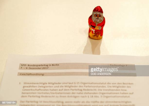 A red chocolate Santa Claus has been posed next to documents at the start of the party congress of Germany's Social Democrats party in Berlin on...