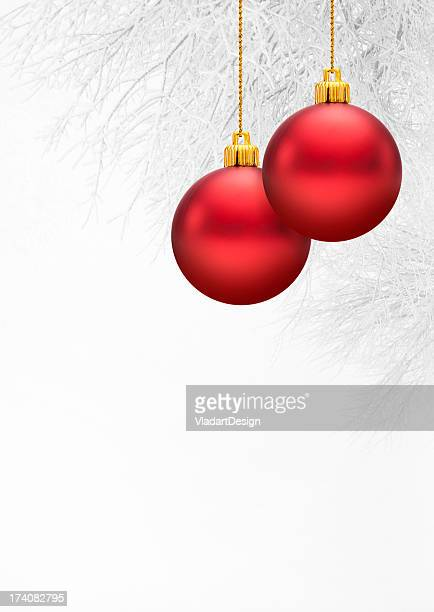 Red Christmas balls with a snow covered branch background