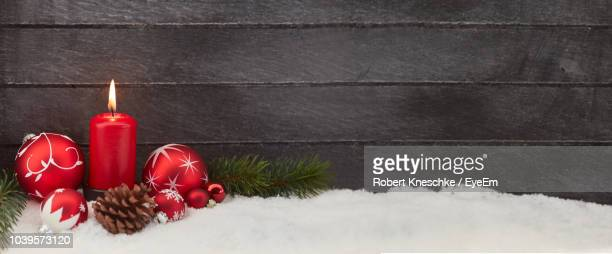 red christmas baubles and lit candle on snow against wall - fake snow stock pictures, royalty-free photos & images