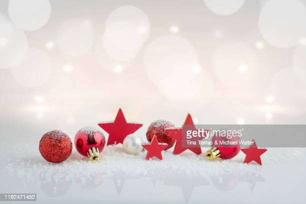 red christmas baubles and red stars decoration on white background with copy space. minimal style. - tina terras michael walter stock-fotos und bilder