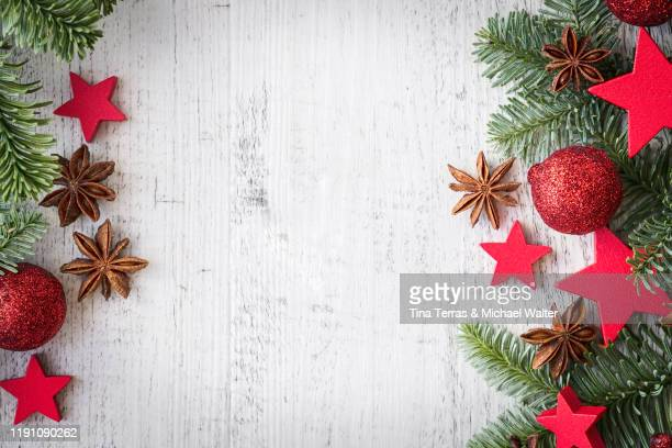 red christmas baubles and red stars decoration on white wooden background with copy space. minimal style. flat lay. - tina terras michael walter stock-fotos und bilder