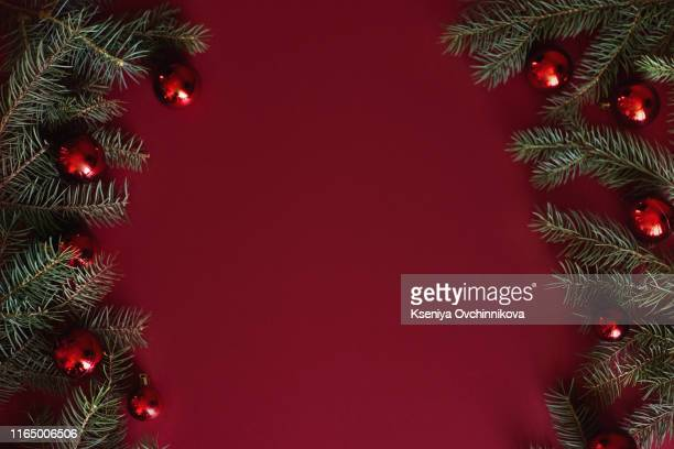 red christmas baubles decoration on red background with copy space. new year greeting card. minimal style. flat lay. - christmas fotografías e imágenes de stock