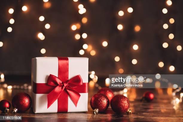 red christmas gift box and baubles on background of defocused golden lights. - geschenk stock-fotos und bilder