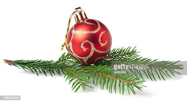 Red Christmas ornament with gold swirls atop a pine branch