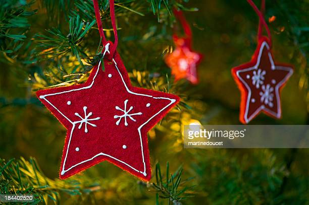 "red christmas stars ornament in tree. - ""martine doucet"" or martinedoucet stock pictures, royalty-free photos & images"