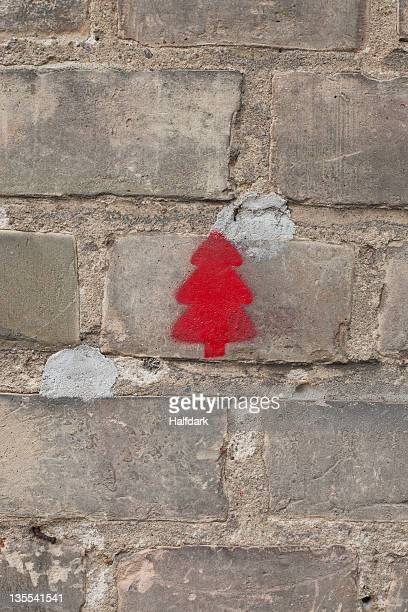 A red Christmas tree stenciled on a brick wall