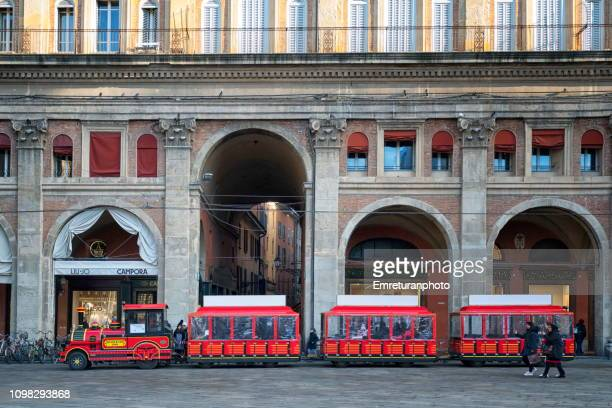 red city tour train at piazza maggiore,bologna. - emreturanphoto stock pictures, royalty-free photos & images