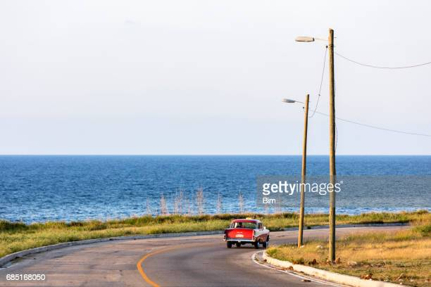 red classic car driving along the coast in cuba - 1957 stock pictures, royalty-free photos & images