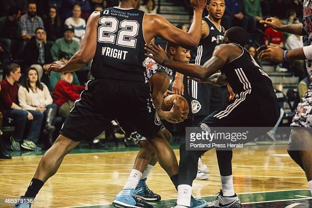 Red Claws guard Tim Frazier is surrounded by Spurs defense forward Keith Wright left guard Orlando Johnson center and guard Jonathan Simmons right at...