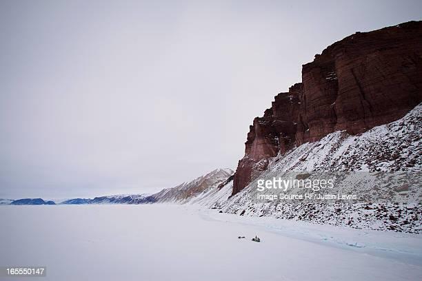 red cliffs in snowy landscape - 犬ぞりに乗る ストックフォトと画像