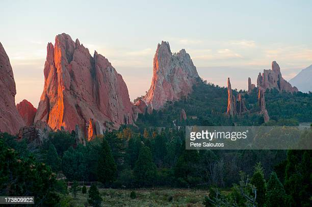 red cliffs rising in rural landscape - garden of the gods stock photos and pictures