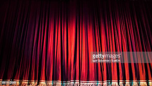 red closed curtain with spotlight in theater - igor golovniov stock pictures, royalty-free photos & images