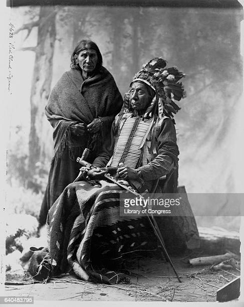 Red Cloud the Sioux Chief who led opposition to the Bozeman Trail through Indian lands sits next to his wife and holds a pipe, 1900.