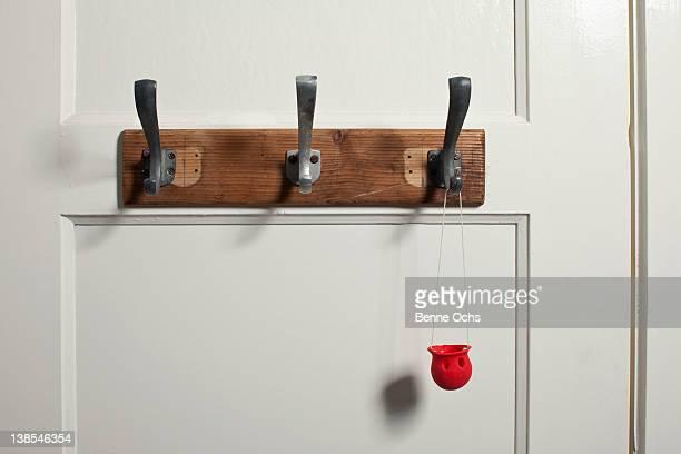 Red clown's nose hanging from coat hook on door