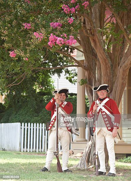 red coats resting in shade - colonial williamsburg stock photos and pictures