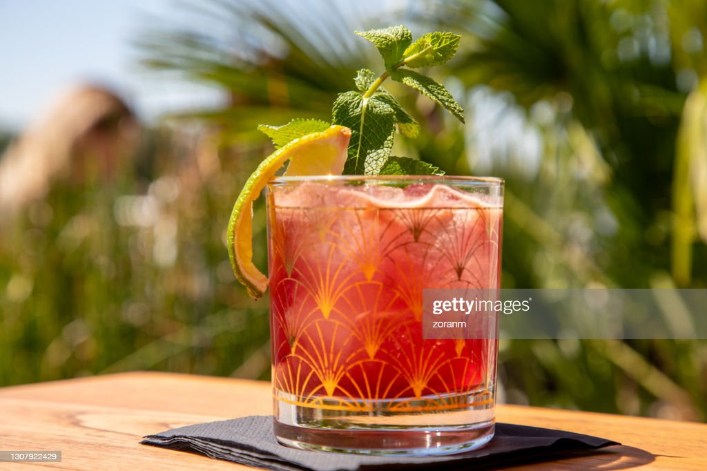 Red cocktail on the rocks with mint leaf and lime peal : Stock Photo