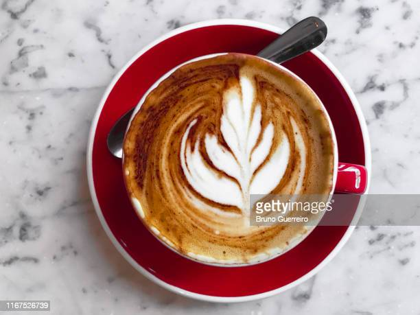 red coffee cup with leaf design on marble stone table seen from above - cappuccino stock pictures, royalty-free photos & images