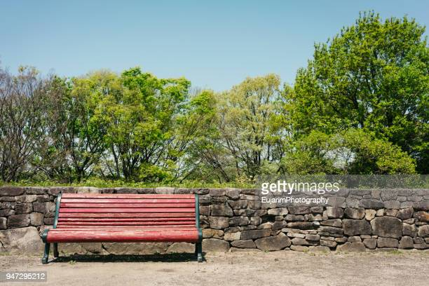 red color bench in the park on a beautiful spring day - stone wall stock pictures, royalty-free photos & images