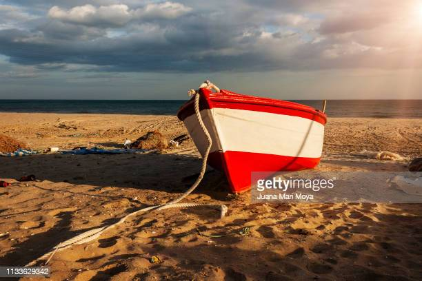 Red colored boat on a beach in Isla Antilla, Huelva. Spain